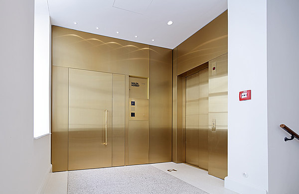 Brass covered fire-rated door EI30, made of forster fuego light steel profiles.