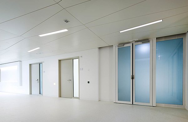Fire-rated doors EI30 as glazed sliding doors with escape route function or as doors with steel frame and wooden door leaf. System: forster fuego light Hospital Münsterligen, Switzerland