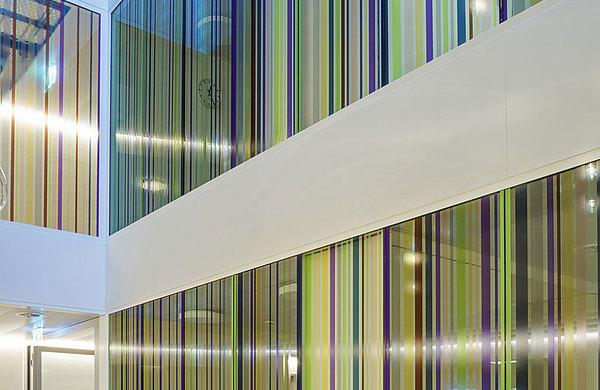 Verglastes Atrium mit forster fuego light Stossfugenverglasung EI60, mit farbigen Folienstreifen dekoriert. Spital Langenthal, Schweiz