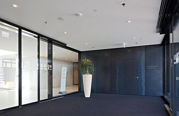 Flächenbündig verblechte Brandschutztüren EI30 aus Stahl und automatische Brandschutzschiebetüren EI30. System: forster fuego light Hotel Säntispark, Schweiz
