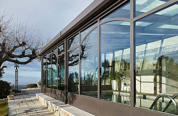 """Schwimmbadverglasung aus Stahlprofilen mit Wärmedämmung. Die grossen Glasflächen mit teilweise dekoativ gebogenen Profilen gewähren einen ungehinderten Blick in die atemberaubende Landschaft. Profilsystem forster unico. Hotel und SPA """"Bastide Tourtour"""" in Frankreich."""
