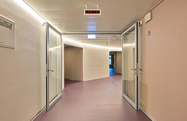 Die grossen Drehflügeltüren mit Magnethalterung schaffen möglichst breite Durchgänge. Auf Grund ihrer sprichwörtlichen Stabilität überstehen die Türen auch  grössere mechanische Belastungen wie Rempler mit den Spitalbetten.  Spital Langenthal, Schweiz